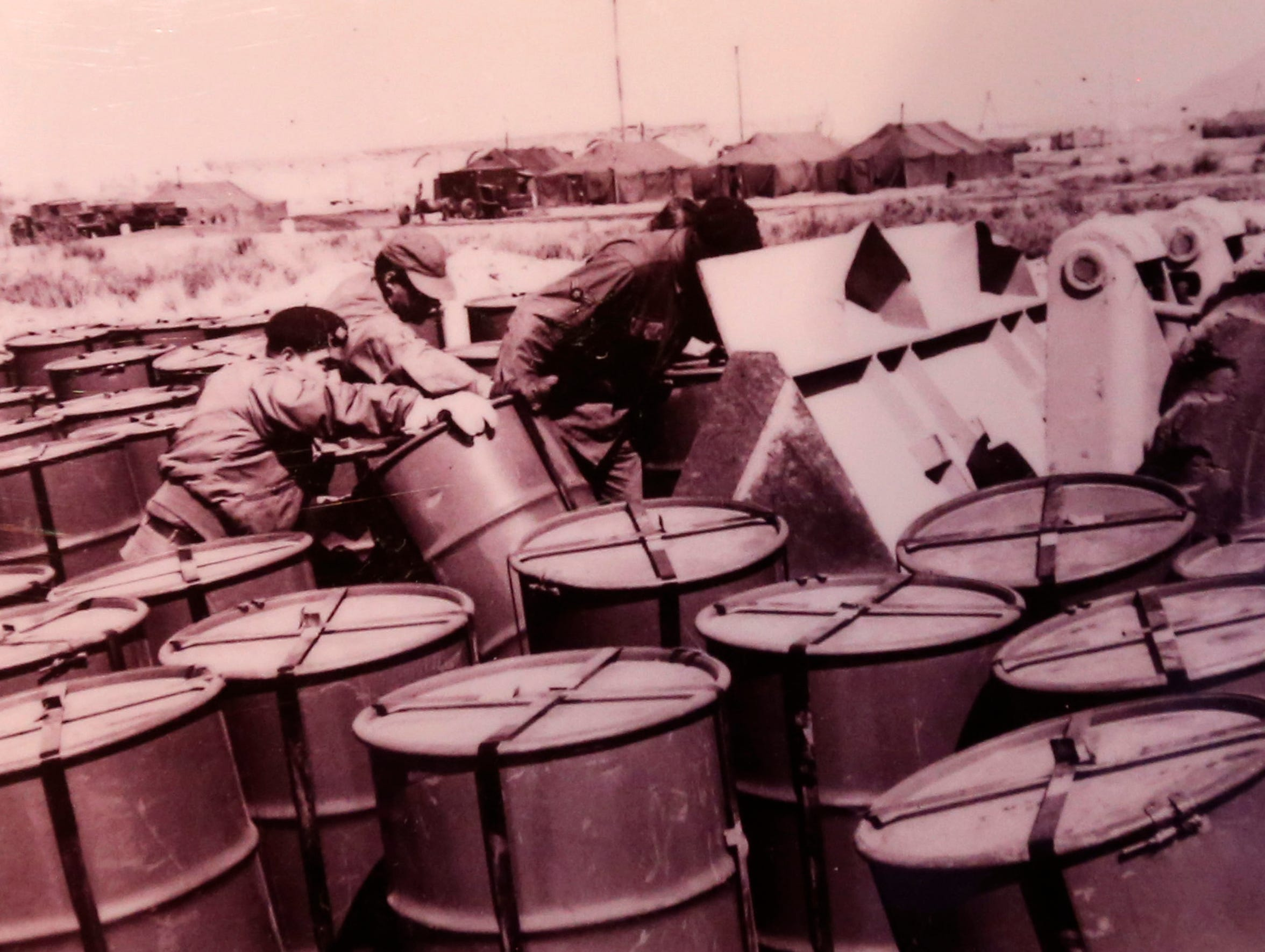 This photo shows soldiers preparing drums that radioactive
