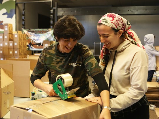 Kosher Troops co-founder Sara Fuerst and her daughter Leah Lapa, 22, pack Passover boxes for soldiers at the warehouse in Suffern March 15, 2018. Kosher Troops started as Lapa's bat mitzvah project 10 years ago.