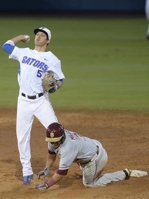 Florida infielder Dalton Guthrie (5) throws to first for a double play as Florida State's Darren Miller (3) slides into second base during the 3rd inning in Gainesville on Friday.