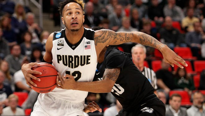 Purdue forward Vincent Edwards (12) looks to make a play defended by Butler guard Henry Baddley (20) in the second round of the 2018 NCAA Tournament at Little Caesars Arena.