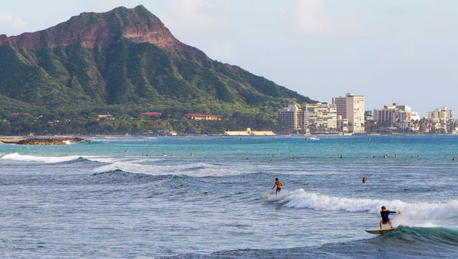 FILE - This Nov. 4, 2014 file photo shows surfers off Ala Moana Beach Park, in Honolulu with Diamond Head mountain in the background. Diamond Head, a volcanic crater located at one end of Waikiki on the coast of Oahu, is one of Hawaii's most famous landmarks as well as one of its most popular tourist attractions. (AP Photo/Marco Garcia, File)