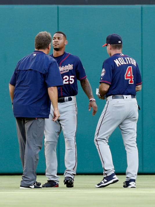 Minnesota Twins center fielder Byron Buxton (25) is checked by a team trainer and manager Paul Molitor (4) after colliding into the outfield wall on a ball hit by Texas Rangers' Rougned Odor during the first inning of a baseball game Friday, July 8, 2016, in Arlington, Texas. (AP Photo/Jim Cowsert)