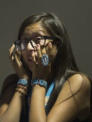 Nichole Segay, 16, wipes her tears after speaking before