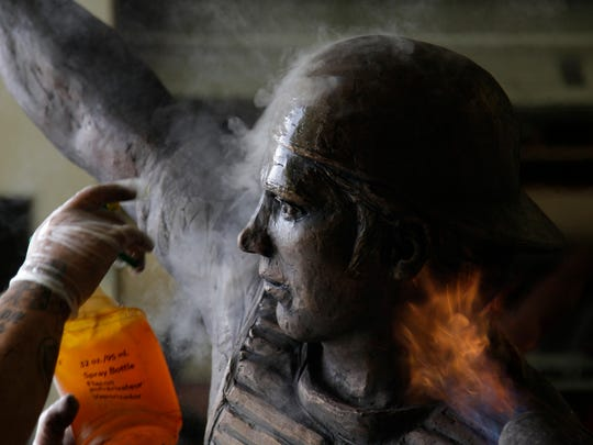Application of heat and liquid applied during the patina process for the Johnny Bench statue.