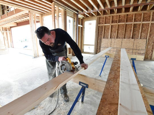 Aaron Melvin owner of AM Carpentry LLC., in Felton makes a cut on a piece of wood for a new home in Rehoboth Beach.