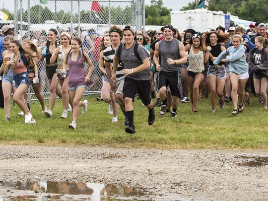 Firefly attendees run in as the gates open at the Firefly Music Festival in Dover on Thursday afternoon.