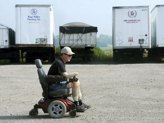 Paul Miller uses his wheelchair to make his way around the property of his trucking business in Spring Grove on Tuesday, August 20, 2013.  Miller was struck with Streptococcus Pneumoniae on Sunday, Feb 3, 2013, which resulted in the amputation of his hands and feet.
