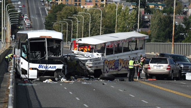 Officers investigate the scene of a crash between a tour bus and a tourist duck boat on the Aurora Bridge in Seattle, Washington on September 24, 2015. Four people were killed.