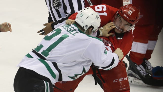 Red Wings defensemen Xavier Ouellet fights against Stars left wing Antoine Roussel during the third period of the Wings' 3-1 win Tuesday at Joe Louis Arena.