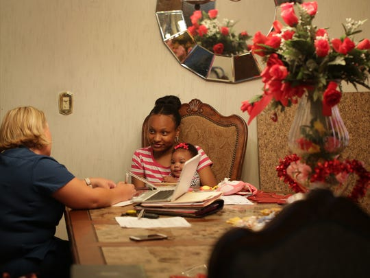 Zaria Wilson, 18, right, and her four-months-old daughter La'Riyah McCollum talk with nurse Wendi Miller during a home visit by the Nurse- Family Partnership in Dillion, SC in June 2016.