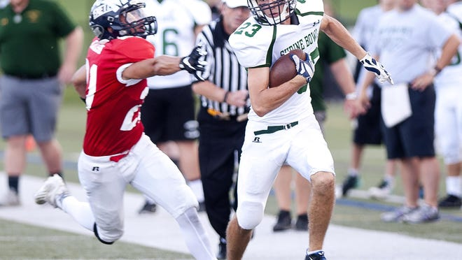 Vermont's Connor Plante, right, eludes a New Hampshire tackler after making a catch in the 63rd annual Shrine Maple Sugar Bowl on Saturday night at Castleton University.