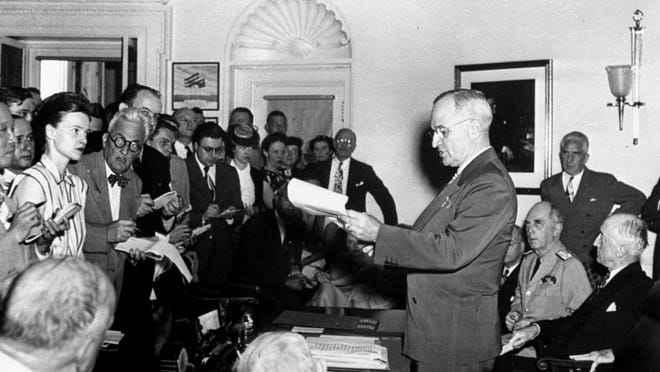 President Harry S Truman of Independence reads his announcement of the Japanese surrender officially signaling the war's end during an Aug. 14, 1945, White House ceremony.  At the right of the President are Secretary of State James F. Byrnes and Admiral William D. Leahy, Presidential Chief of Staff.