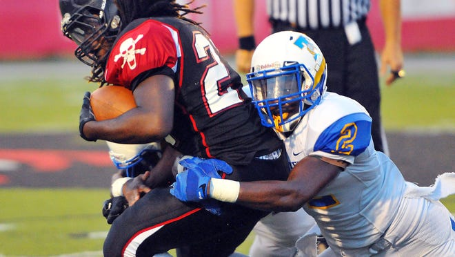 Palm Bay High's Sekai Lindsay is taken down by Titusville's James Lowder during Friday night's game.