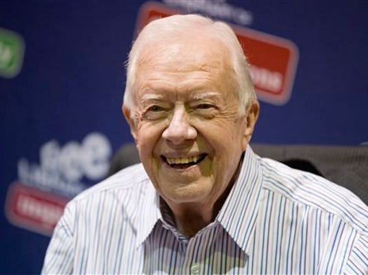 """FILE - In this July 10, 2015, file photo, former President Jimmy Carter poses for photographs at an event for his new book """"A Full Life: Reflections at Ninety at the Free Library in Philadelphia. Carter is expected to make a full recovery after having an operation Monday, Aug. 3, to remove a small mass in his liver, according to a spokeswoman."""