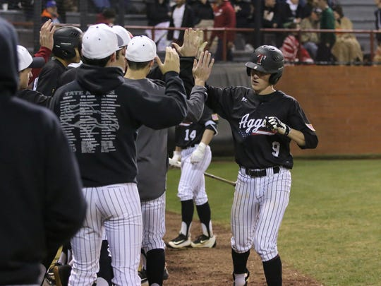 Tate's Mason Land (9) gets congratulated by felow Aggies after scoring against Coweta on a bad throw to second base during the 2017 Aggie Classic Tuesday night at Tate High School.
