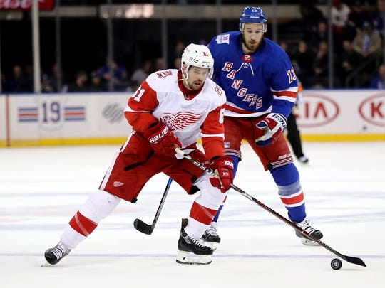 Red Wings defenseman Xavier Ouellet takes the puck as the Rangers' Kevin Hayes defends on Sunday, Feb. 25, 2018, in New York.