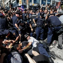 Police and protesters fall to ground during demonstration, Wednesday, July 20, 2016, in Cleveland, during the third day of the Republican convention. (AP Photo/John Minchillo)