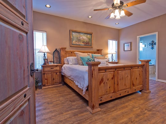 A rustic wood door leads into the spacious master bedroom.