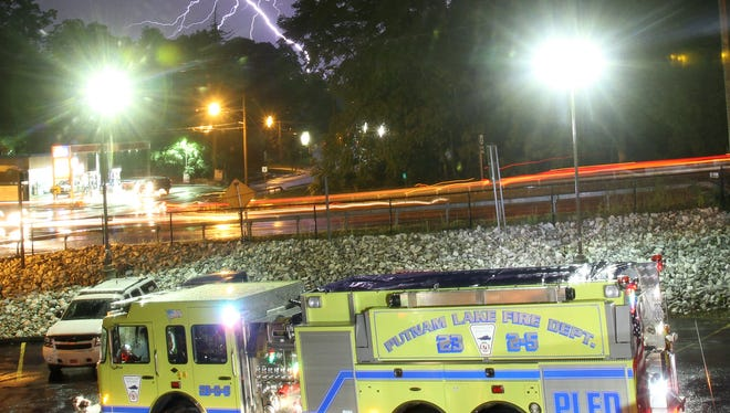 A flash of lightning strikes near the end of the Brewster Fire Department parade during an evening storm Wednesday, July 23.
