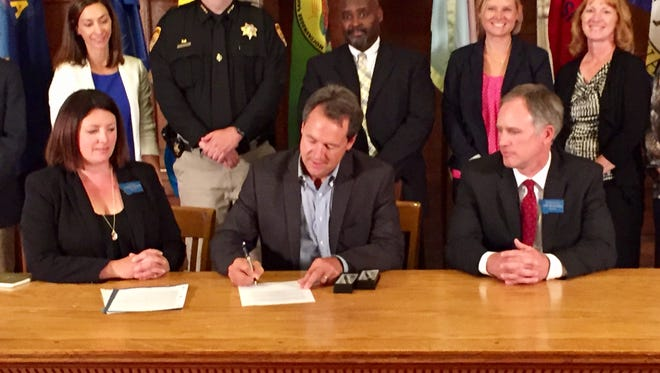 Gov. Steve Bullock, seated at center, signs crime bills Wednesday. Seated at left is Sen. Cynthia Wolken, D-Missoula.
