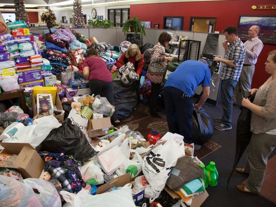 Employees at The Spectrum and members of the Washington County School District gather donations for the Step Up St. George drive Tuesday, Dec. 6, 2016.