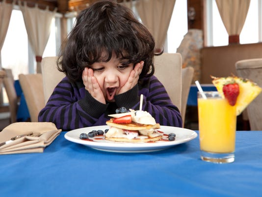 Ecstatic young boy eating a stack of pancakes