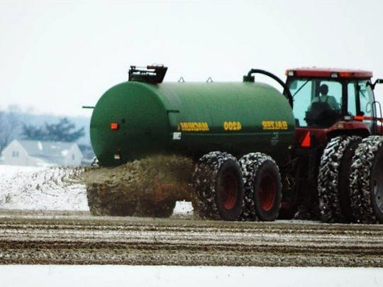 A farmer applies manure to his fields.