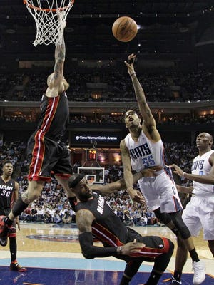 Charlotte Bobcats' Chris Douglas-Roberts, right, is fouled as he drives to the basket against Miami Heat's LeBron James, center, and Chris Andersen, left, during the second half in Game 4 of an opening-round NBA basketball playoff series in Charlotte, N.C., Monday, April 28, 2014. The Heat won 109-98. (AP Photo/Chuck Burton)