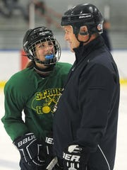 Assistant coach Owen McIntee, right, talks with his 13-year-old daughter Maddie during a practice at Webster Ice Arena.