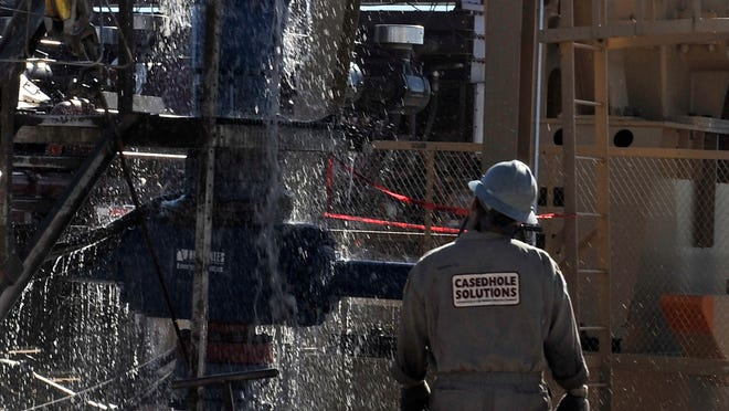 Water gushes out of a drilling pipe as it is pulled up to be replaced with a fresh pipe at a hydraulic fracturing site in Midland, Texas, on Sept. 24. The drilling method known as fracking uses huge amounts of high-pressure, chemical-laced water to free oil and natural gas trapped deep in underground rocks.