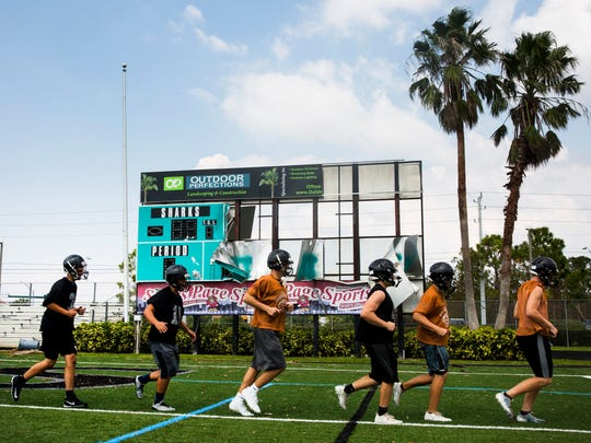 Players run past the destroyed scoreboard during practice at Gulf Coast High School in Naples on Wednesday, Sept. 20, 2017.