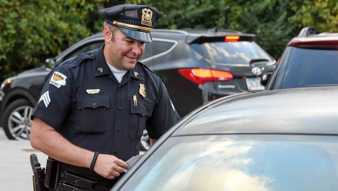 West Des Moines Police Officer Giampollo talks with folks as they go through the drive thru on Friday, September 18, 2015, during Cop On Top, were officers from the West Des Moines Police Department and other metro law enforcement agencies take to the sky atop the Dunkin' Donuts at 1301 8th Street, West Des Moines to raise funds for Special Olympics Iowa.