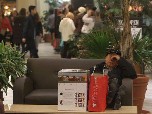 Bob Ruane of Penfield waits for his wife and closes his eyes for a little bit during Black Friday shopping at Eastview Mall in Victor.