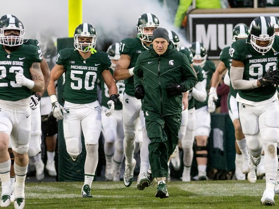 Michigan State head coach Mark Dantonio takes the field