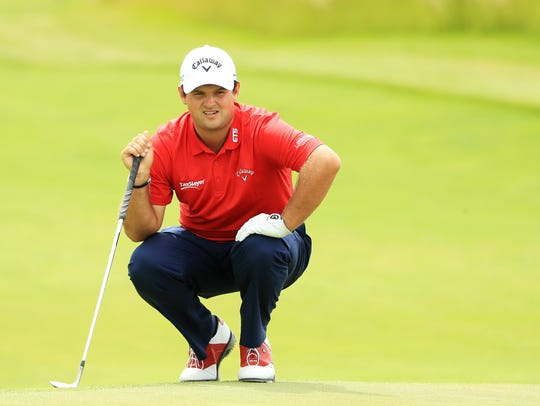 Patrick Reed lines up a putt on the 17th green during