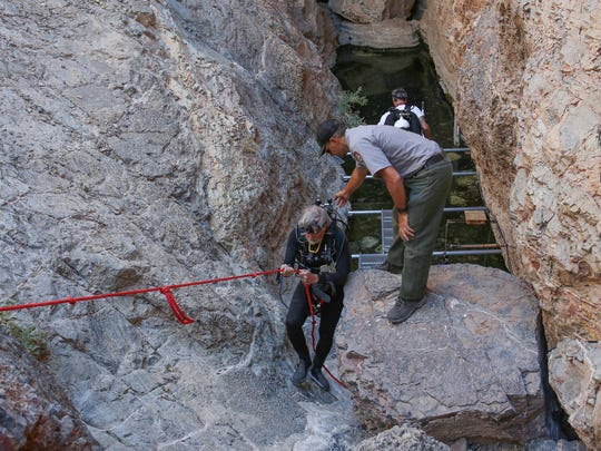 Dr. Stan Hillyard descends the steep embankment at Devil's Hole geothermal pool in Death Valley National Park, September 24, 2016.