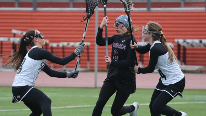 Scarsdale's Jilly Mehlman is pressured by White Plains' Amanda Broderick and Kyra Broderick during their girls lacrosse game at White Plains High School, April 6, 2016.