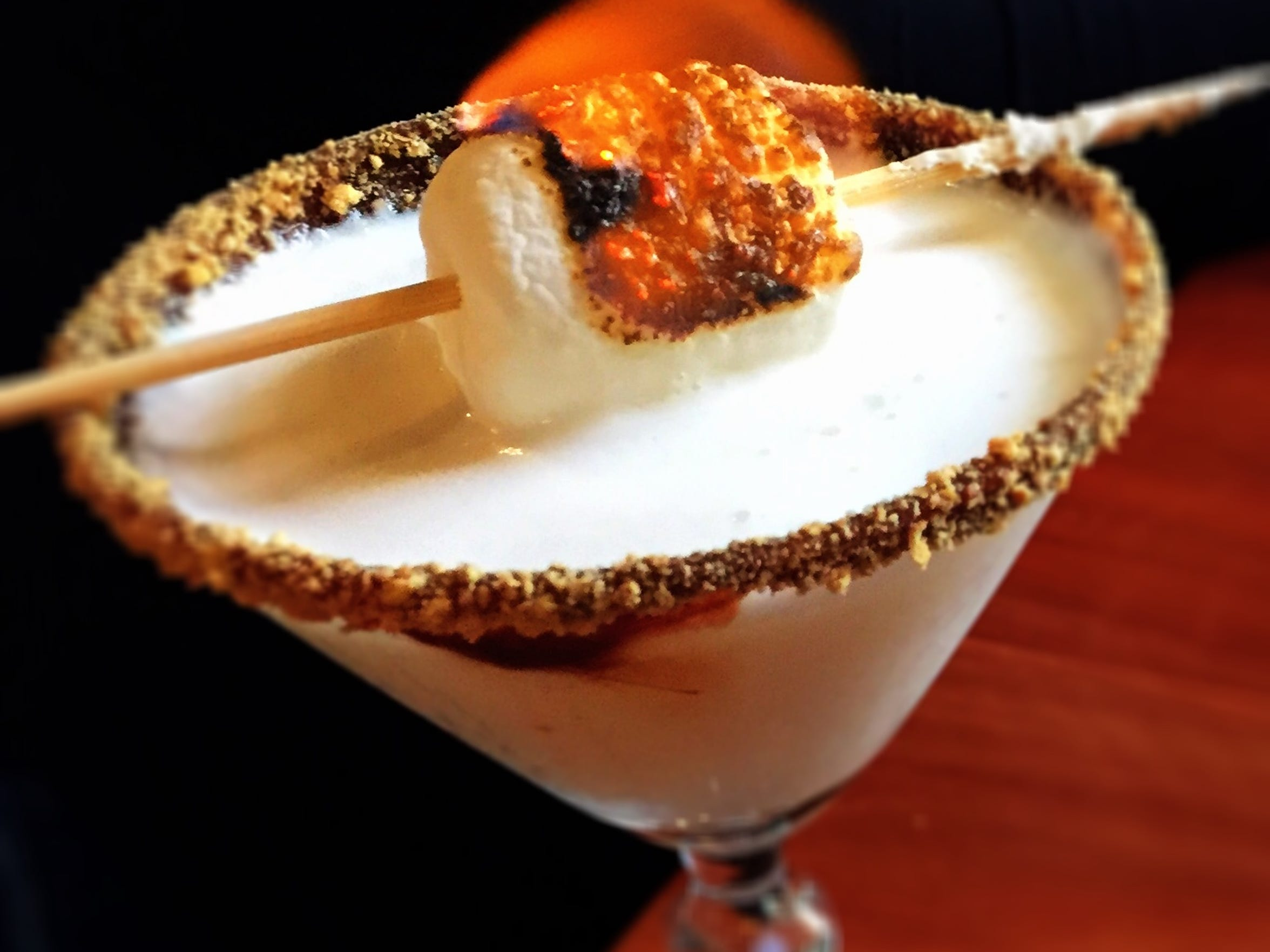 The fireside chat cocktail at Enbar includes a burning marshmallow and a chocolate/graham rim.