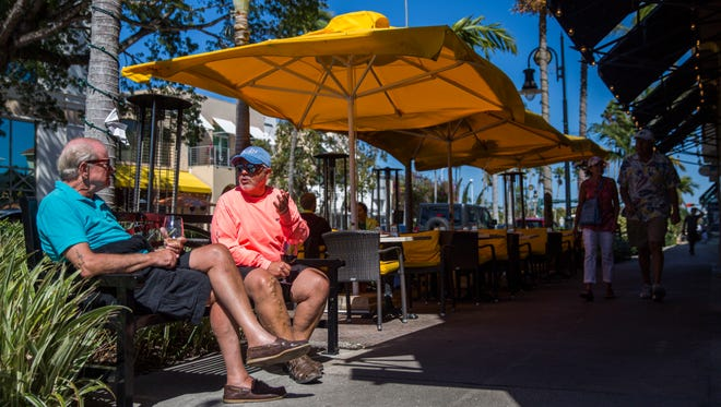 Tim Dilllon, left, and Pat Dougherty, right, enjoy a glass of wine outside of Caffe Milano on 5th Avenue in Naples on Wednesday, March 21, 2018.
