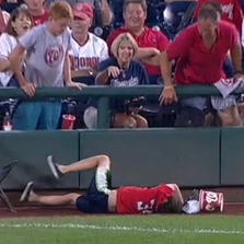 Nationals fan with popcorn a bucket on his head got hit by a foul ball.