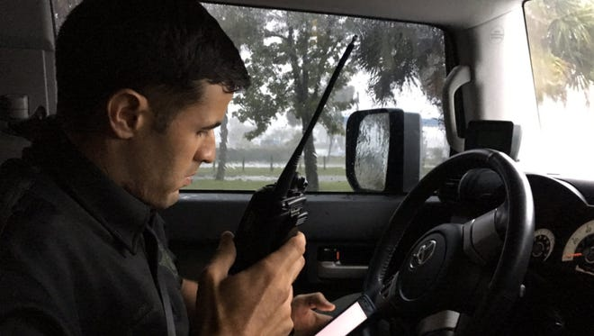 Martin County Sheriff's Office Sgt. Joe Collazo checks his next emergency call on Sunday, Sept. 10, 2017, during Hurricane Irma.