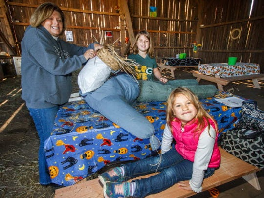 Tenley Morris (foreground), 5, and sister Rachel, 8, of Milwaukee help their grandmother Mary Dargene build a scarecrow at Shady Maple Farm in Sussex.