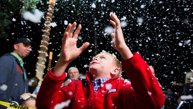 "Will Kramer, 9, looks up towards the ""snow"" during the annual Christmas on Third celebration in downtown Naples on Nov. 21, 2016."