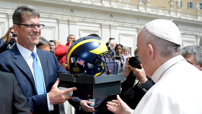 Pope Francis receives a helmet from Michigan coach Jim Harbaugh on April 26, 2017 during the Pontiff weekly audience at the Vatican.