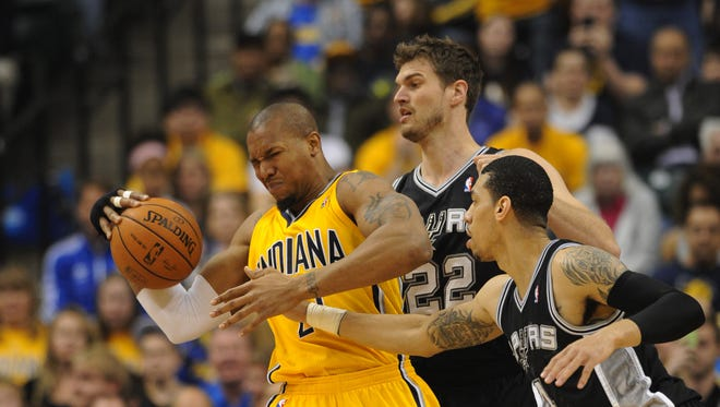 Indiana's David West battles for possession of the ball with San Antonio's Tiago Splitter and Danny Green in the second quarter as the Indian Pacers hosted the San Antonio Spurs at Bankers Life Fieldhouse Monday March 31, 2014.