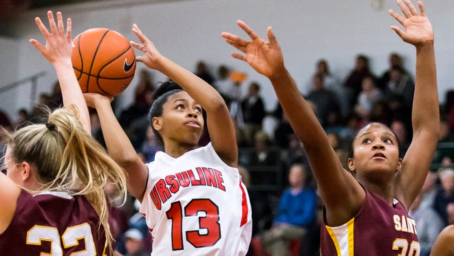 Ursuline Academy's Sabriya Harris (No. 13) puts up a shot between St. Elizabeth's Alexis Bromwell (No. 32) and Alanna Speaks (No. 30) in the second quarter of Ursuline's 60-38 win over St. Elizabeth at Ursuline Academy on Tuesday night.