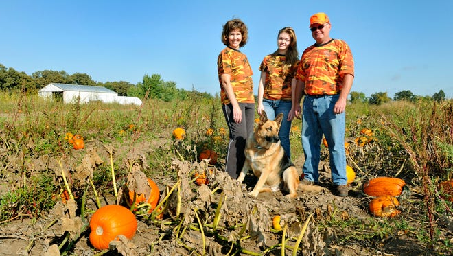 Patty and Utley Kronenberg stand with their daughter Cassondra, 15, in their pumpkin patch Sept. 20 at Sleepy Hollow Farms.