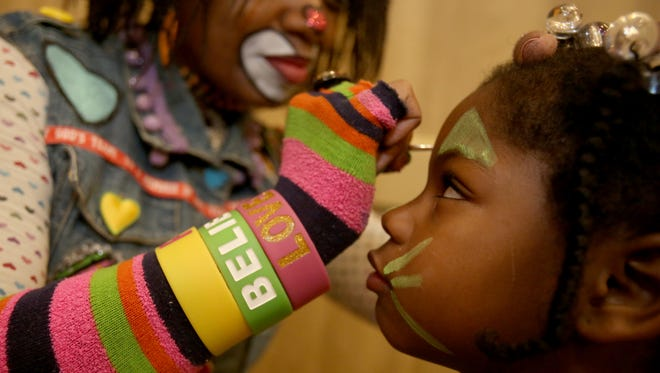 (L to R) Dawn Wilson-Clark of Detroit who plays Kuddles the Clown works at painting the face of Ramiyah Johnson, 5 of Detroit on Saturday, Dec. 5, 2015.