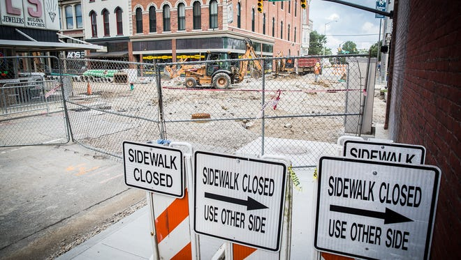 A construction crew works on Walnut Street in downtown Muncie Friday afternoon.
