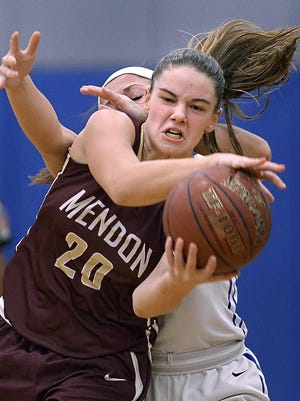 Pittsford Mendon's Sara Lyons, front, grabs a long pass while pressured by Irondequoit's Maria Marcera during regular season game played at Irondequoit High School on Friday, January 22, 2016.